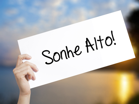 Sonhe Alto! (Dream Big in Portuguese) Sign on white paper. Man Hand Holding Paper with text. Isolated on sunset background. Business concept. Stock Photo