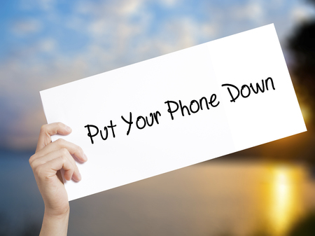 avoidance: Put Your Phone Down Sign on white paper. Man Hand Holding Paper with text. Isolated on sunset background.   Business concept. Stock Photo Stock Photo