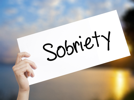 Sobriety Sign on white paper. Man Hand Holding Paper with text. Isolated on sunset background.   Business concept. Stock Photo