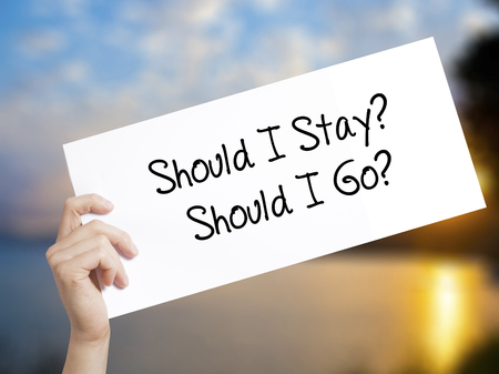 Should I Stay? Should I Go? Sign on white paper. Man Hand Holding Paper with text. Isolated on sunset background.   Business concept. Stock Photo