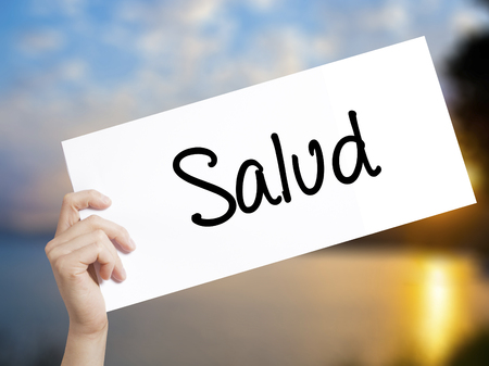 Salud (Health in Spanish) Sign on white paper. Man Hand Holding Paper with text. Isolated on sunset background.  Business concept. Stock Photo