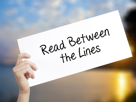 Read Between the Lines   Sign on white paper. Man Hand Holding Paper with text. Isolated on sunset background.   Business concept. Stock Photo Stock Photo