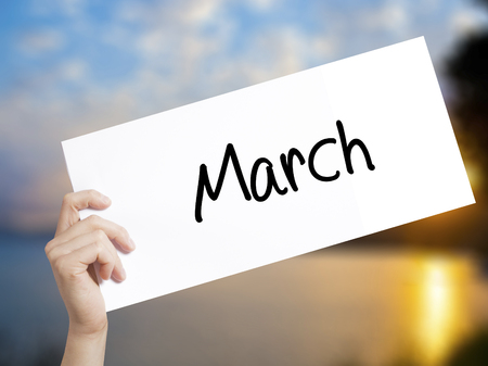 March Sign on white paper. Man Hand Holding Paper with text. Isolated on sunset background.   Business concept. Stock Photo