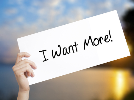 I Want More! Sign on white paper. Man Hand Holding Paper with text. Isolated on sunset background.   Business concept. Stock Photo