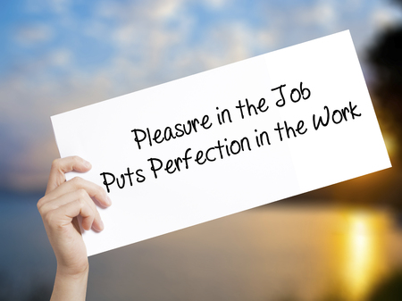 perfectionist: Pleasure in the Job Puts Perfection in the Work Sign on white paper. Man Hand Holding Paper with text. Isolated on sunset background.  Business concept. Stock Photo