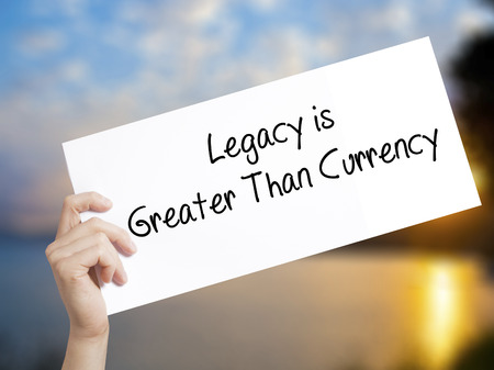 descendants: Legacy is Greater Than Currency Sign on white paper. Man Hand Holding Paper with text. Isolated on sunset background.  Business concept. Stock Photo
