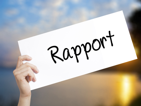 Rapport Sign on white paper. Man Hand Holding Paper with text. Isolated on sunset background.   Business concept. Stock Photo Stock Photo
