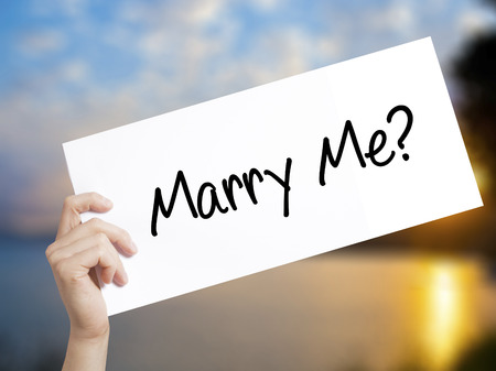 Marry Me? Sign on white paper. Man Hand Holding Paper with text. Isolated on sunset background. Isolated on background. Business, technology, internet concept. Stock  Photo Stock Photo