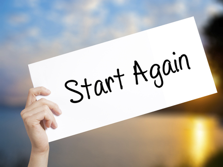 Start Again Sign on white paper. Man Hand Holding Paper with text. Isolated on sunset background.  Business concept. Stock Photo