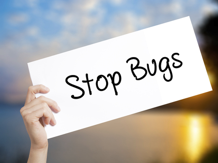 pest control: Stop Bugs Sign on white paper. Man Hand Holding Paper with text. Isolated on sunset background.  Business concept. Stock Photo
