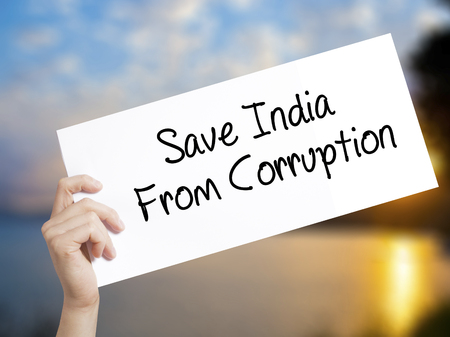 favor: Save India From Corruption Sign on white paper. Man Hand Holding Paper with text. Isolated on sunset background.  Business concept. Stock Photo Stock Photo