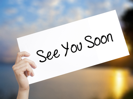 See You Soon Sign on white paper. Man Hand Holding Paper with text. Isolated on sunset background.  Business concept. Stock Photo