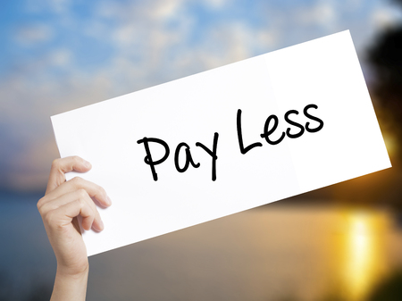 saving tips: Pay Less  Sign on white paper. Man Hand Holding Paper with text. Isolated on sunset background.  Business concept. Stock Photo Stock Photo