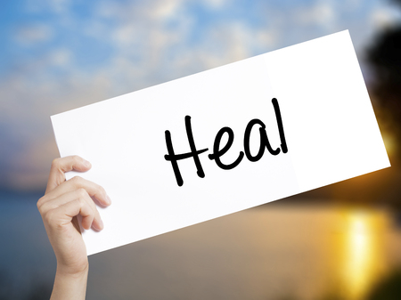 healer: Heal  Sign on white paper. Man Hand Holding Paper with text. Isolated on sunset background.  Business concept. Stock Photo