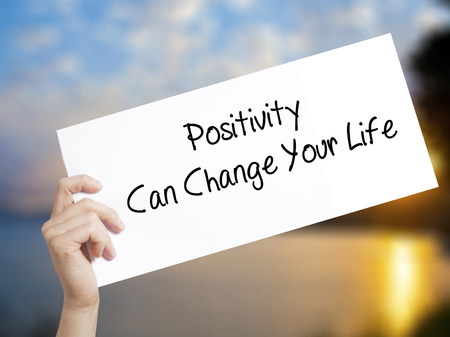 Positivity Can Change Your Life Sign on white paper. Man Hand Holding Paper with text. Isolated on sunset background.  Business concept. Stock Photo Stock Photo