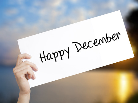 Happy December Sign on white paper. Man Hand Holding Paper with text. Isolated on sunset background.   Business concept. Stock Photo