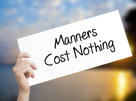 Manners Cost Nothing Sign on white paper. Man Hand Holding Paper with text. Isolated on sunset background.   Business concept. Stock Photo Stock Photo