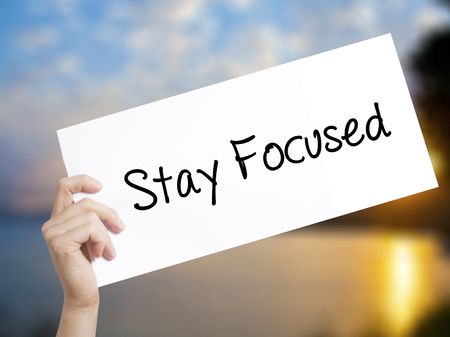 Stay Focused Sign on white paper. Man Hand Holding Paper with text. Isolated on sunset background. Isolated on background. Business,   Business concept. Stock Photo