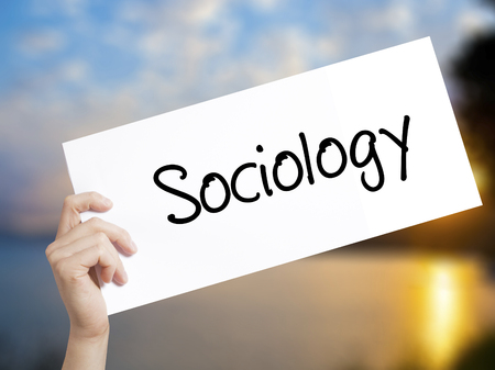 infeasible: Sociology  Sign on white paper. Man Hand Holding Paper with text. Isolated on sunset background.  Business concept. Stock Photo