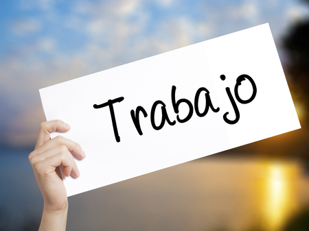 Trabajo  ( work in Spanish) Sign on white paper. Man Hand Holding Paper with text. Isolated on sunset background.  Business concept. Stock Photo