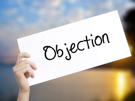 objection: Objection Sign on white paper. Man Hand Holding Paper with text. Isolated on sunset background.  Business concept. Stock Photo Stock Photo