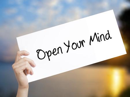 Öffnen Sie Ihr Mind Sign auf weißem Papier. Mann-Hand, die Papier mit Text hält. Auf Sonnenuntergang Hintergrund isoliert. Geschäftskonzept. Foto auf Lager