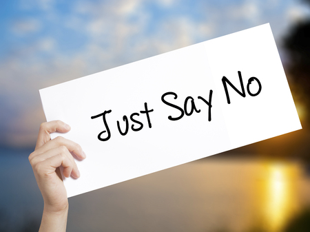 hand holding paper: Just Say No Sign on white paper. Man Hand Holding Paper with text. Isolated on sunset background.   Business concept. Stock Photo Stock Photo