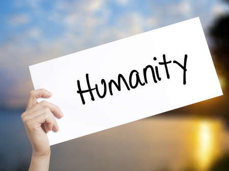 clemency: Humanity  Sign on white paper. Man Hand Holding Paper with text. Isolated on sunset background.  Business concept. Stock Photo Stock Photo