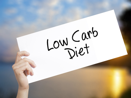 carbohydrates: Low Carb Diet Sign on white paper. Man Hand Holding Paper with text. Isolated on sunset background.   Business concept. Stock Photo