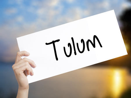 Tulum Sign on white paper. Man Hand Holding Paper with text. Isolated on sunset background.   Business concept. Stock Photo