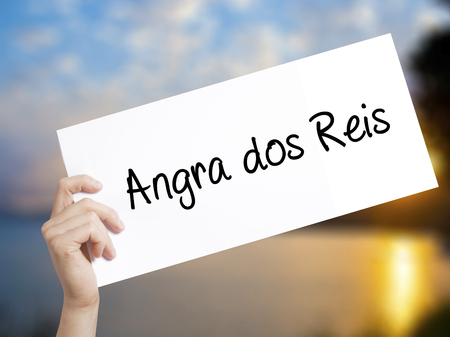 Angra dos Reis Sign on white paper. Man Hand Holding Paper with text. Isolated on sunset background.   Business concept. Stock Photo
