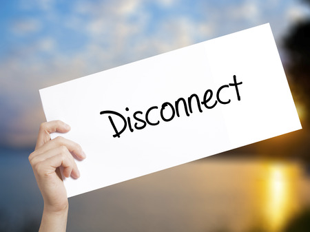 Disconnect Sign on white paper. Man Hand Holding Paper with text. Isolated on sunset background.   Business concept. Stock Photo