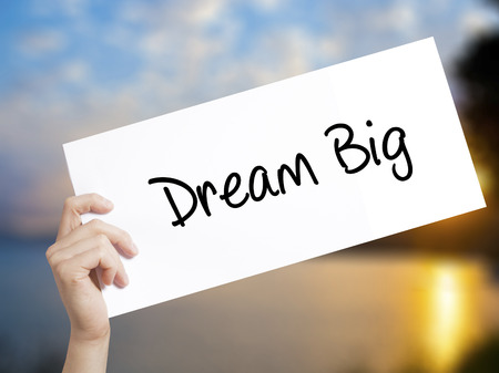 Dream Big  Sign on white paper. Man Hand Holding Paper with text. Isolated on sunset background.   Business concept. Stock Photo