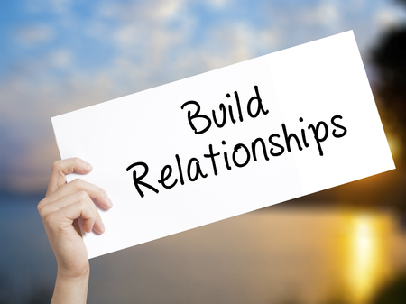 middleman: Build Relationships Sign on white paper. Man Hand Holding Paper with text. Isolated on sunset background.  Business concept. Stock Photo Stock Photo