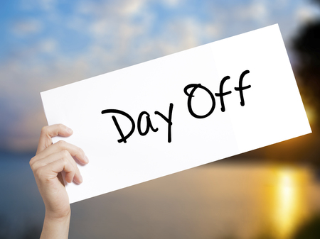 Day Off  Sign on white paper. Man Hand Holding Paper with text. Isolated on sunset background.  Business concept. Stock Photo Stock Photo