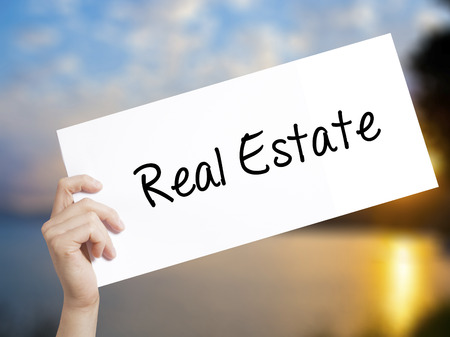 finer: Real Estate  Sign on white paper. Man Hand Holding Paper with text. Isolated on sunset background.   Business concept. Stock Photo