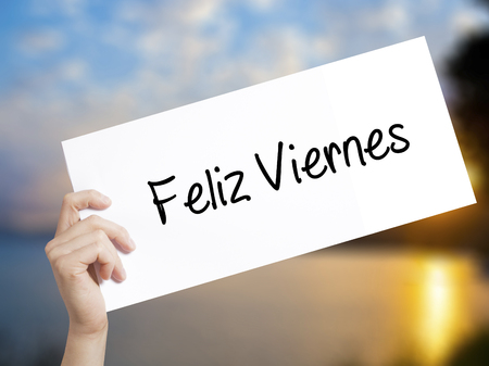 Feliz Viernes (Happy Friday In Spanish)  Sign on white paper. Man Hand Holding Paper with text. Isolated on sunset background.  Business concept. Stock Photo