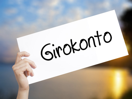 girokonto: Girokonto (Checking Account) Sign on white paper. Man Hand Holding Paper with text. Isolated on sunset background.  Business concept. Stock Photo Stock Photo