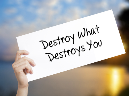annihilate: Destroy What Destroys You Sign on white paper. Man Hand Holding Paper with text. Isolated on sunset background.  Business concept. Stock Photo