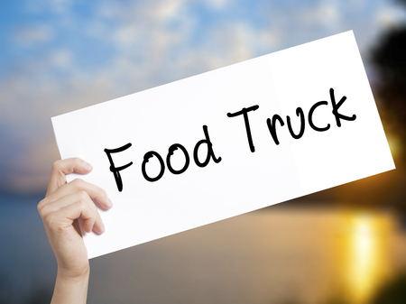 famous industries: Food Truck Sign on white paper. Man Hand Holding Paper with text. Isolated on sunset background.  Business concept. Stock Photo Stock Photo