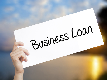 borrowing: Business Loan Sign on white paper. Man Hand Holding Paper with text. Isolated on sunset background.   Business concept. Stock Photo