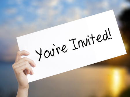 Youre Invited! Sign on white paper. Man Hand Holding Paper with text. Isolated on sunset background.  Business concept. Stock Photo