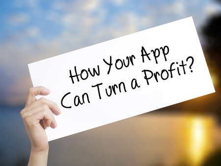 How Your App Can Turn a Profit? Sign on white paper. Man Hand Holding Paper with text. Isolated on sunset background.  Business concept. Stock Photo Reklamní fotografie