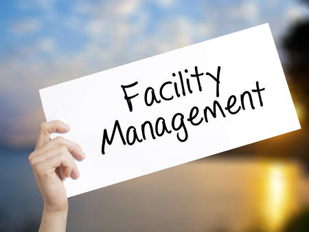 property management: Facility Management Sign on white paper. Man Hand Holding Paper with text. Isolated on sunset background.   Business concept. Stock Photo
