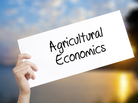 Agricultural Economics Sign on white paper. Man Hand Holding Paper with text. Isolated on sunset background.   Business concept. Stock Photo