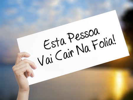 Esta Pessoa Vai Cair Na Folia! (This Person Will be at Carnaval in Portuguese) Sign on white paper. Man Hand Holding Paper with text. Isolated on sunset background.  Business concept. Stock Photo Imagens