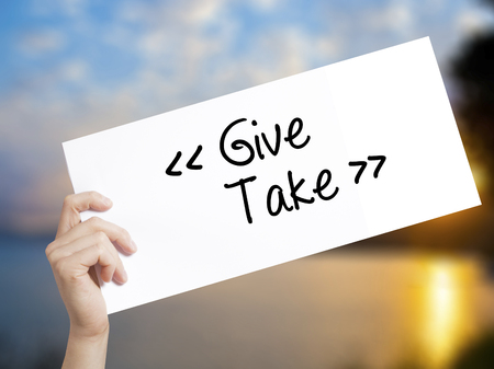 Give - Take Sign on white paper. Man Hand Holding Paper with text. Isolated on sunset background.  Business concept. Stock Photo