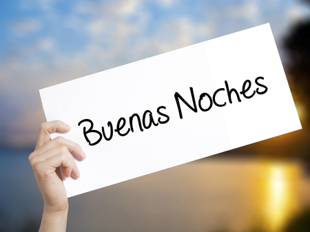 Buenas Noches (Good Night In Spanish)Sign on white paper. Man Hand Holding Paper with text. Isolated on sunset background.  Business concept. Stock Photo