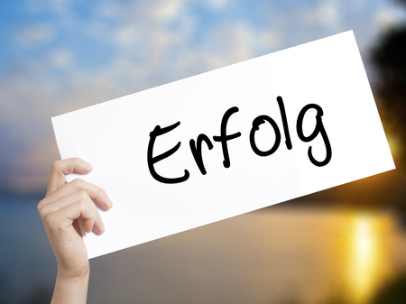 Erfolg Success (in German) Sign on white paper. Man Hand Holding Paper with text. Isolated on sunset background.   Business concept. Stock Photo Stock Photo