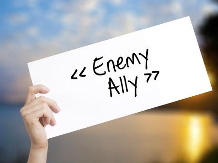 Enemy - Ally Sign on white paper. Man Hand Holding Paper with text. Isolated on sunset background.  Business concept. Stock Photo